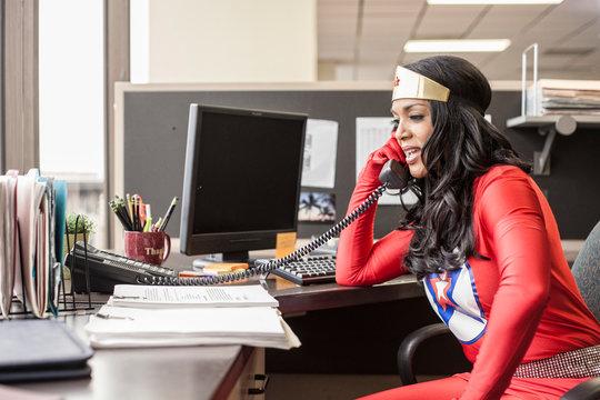 Businesswoman in super hero costume working in office
