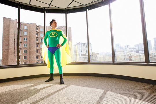 Businessman in super hero costume looking through window