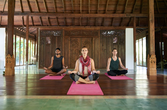 Three multi-ethnic people sitting in lotus pose practicing yoga together in a traditional temple in Bali Indonesia