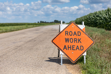 Road work ahead sign on barricade on rural country asphalt road