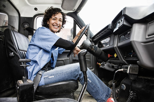 Smiling driver sitting in delivery truck