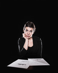 Portrait of woman with documents sitting indoors