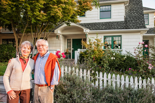 Portrait of smiling couple standing outside new home