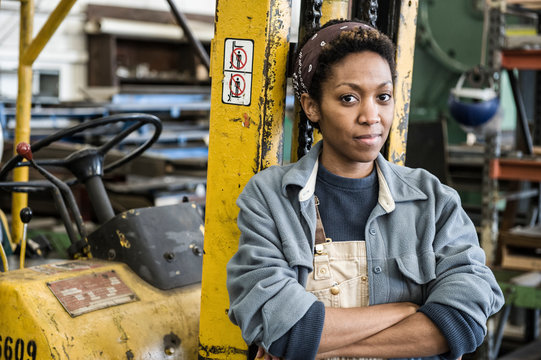 Portrait of woman leaning on forklift in factory