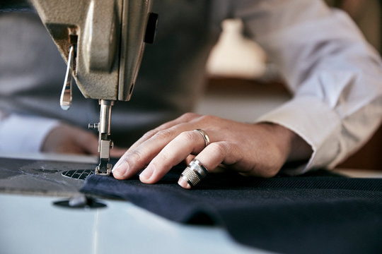 Midsection of man sewing garment on sewing machine