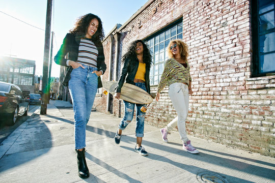 Smiling friends walking on sidewalk in city