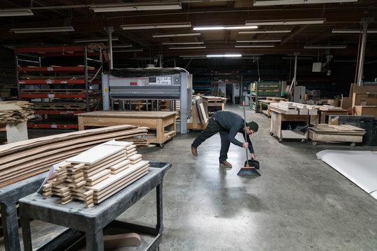 Worker cleaning floor in workshop
