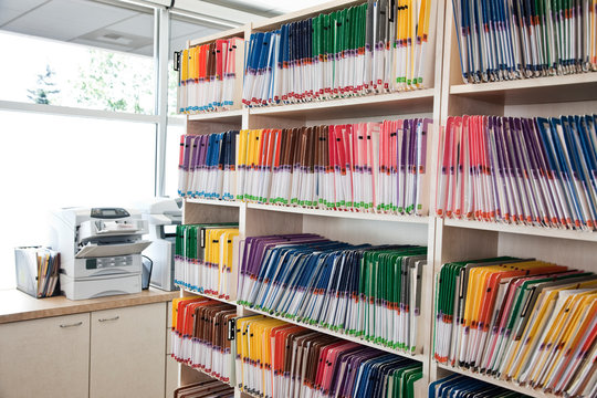 View of colorful file folders arranged on shelf in dental office