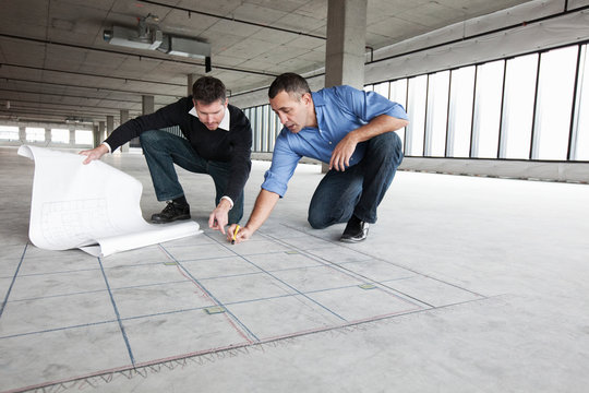 Architect and businessman drawing plan on concrete floor