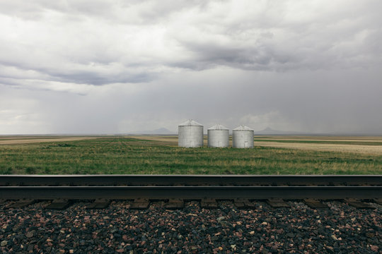 Stormy clouds over grain silos on farmland with rail track in foreground