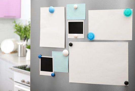 Sheets of paper and photos with magnets on refrigerator door indoors. Space for text