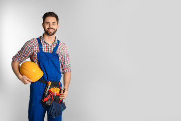 Fototapeta Portrait of construction worker with tool belt on light background. Space for text obraz