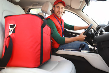 Male courier with thermo bag in car. Food delivery service