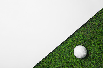 Golf ball and white paper on green artificial grass, top view with space for text