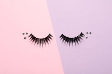 False eyelashes and sparkles on color background, flat lay