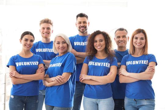 Team of volunteers in uniform on light background