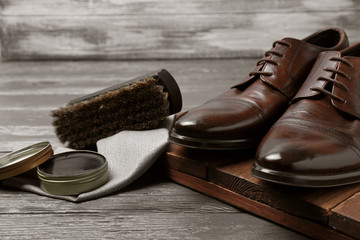 Footwear and shoe shine kit on grey table