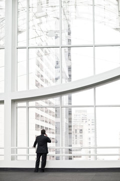Rear view of businessman talking on smartphone in office lobby