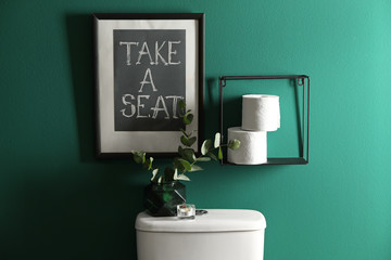 Decor elements, paper rolls and toilet bowl near green wall. Bathroom interior Wall mural