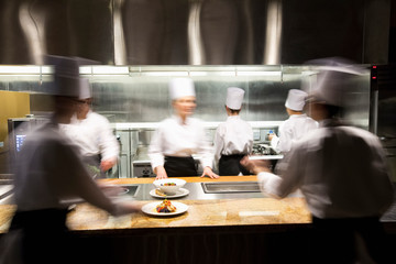 Blurred motion of crew of chef's working in commercial kitchen