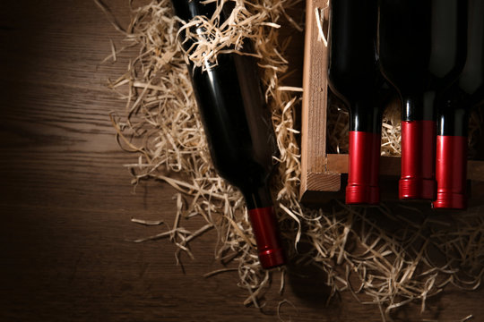 Flat lay composition with crate and bottles of wine on wooden table