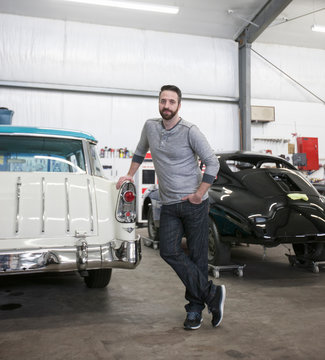 Portrait of mechanic standing in automobile repair shop