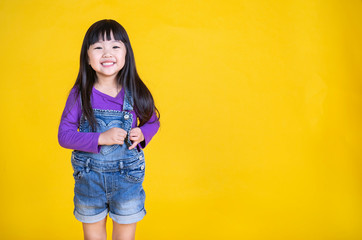 Portrait of young happy little asian girl in uniform isolated on yellow background with copy space. Education for toddler or preschool, childhood lifestyle back to school concept