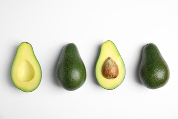 Cut and whole fresh ripe avocados on white background, top view