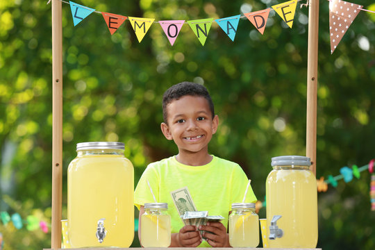 Cute little African-American boy with money at lemonade stand in park. Summer refreshing natural drink