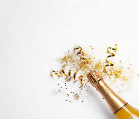 Bottle of champagne with gold glitter, confetti and space for text on white background, top view. Hilarious celebration