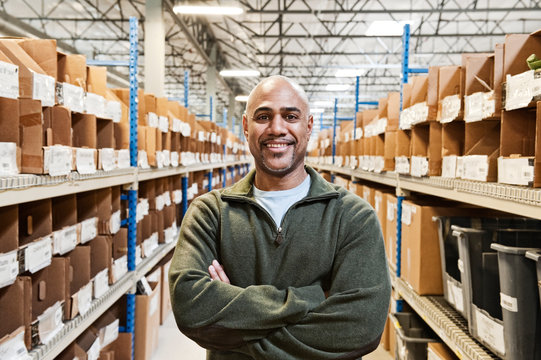 Portrait of smiling worker standing in warehouse