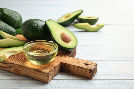 Board with bowl of natural oil and avocados on white wooden background. Space for text