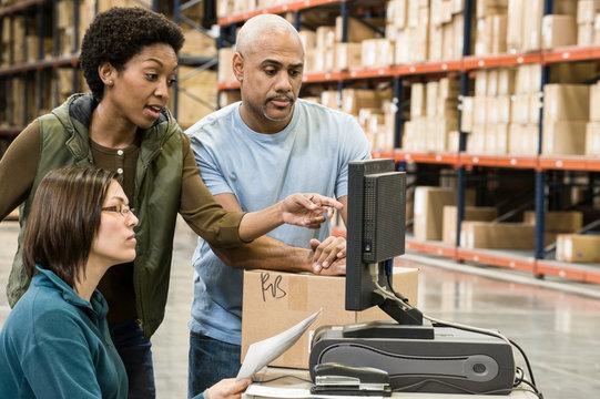 Workers working on desktop computer in warehouse