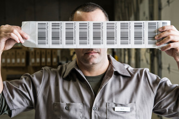 Worker holding sheet of barcode labels in warehouse