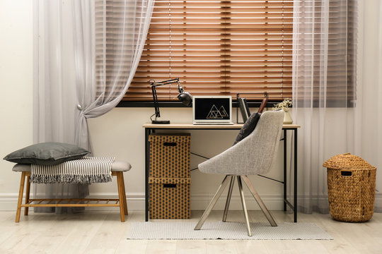 Comfortable workplace near window with horizontal wooden blinds