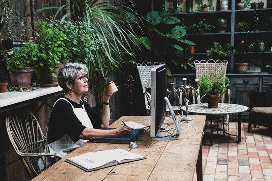 Senior woman having coffee while working on desktop computer