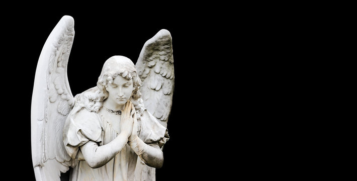Guardian angel sculpture with open wings isolated on wide panorama banner black background with empty text space. Angel sad expression sculpture with eyes down and hands together in front of chest.