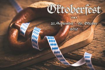 Oktoberfest 2019 Banner mit Brezel und bayrischem Tischtuch auf Holzuntergrund