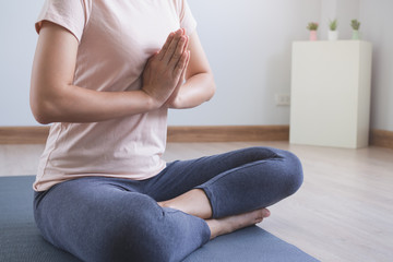 Yoga and meditation lifestyles. close up view of young beautiful woman practicing yoga namaste pose in the living room at home.