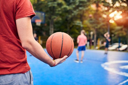 Man holding basketball ball on the urban city court.