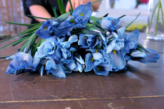 Creating professional bunch. Florist woman making bouquet from blue iris flowers on table for sale in shop, hands closeup. Working in floristic studio store. Floral business concept.