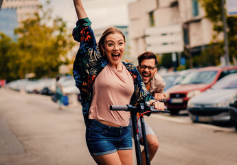 Young couple on vacation having fun driving electric scooter through the city.	 Wall mural