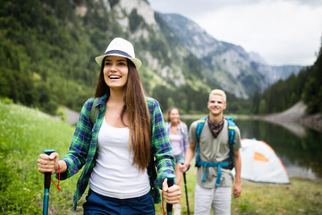 Fototapeta Group of happy friends with backpacks hiking together