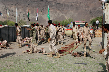 Soldiers lie on the ground after a missile attack on a military parade during a graduation ceremony for newly recruited troopers in Aden
