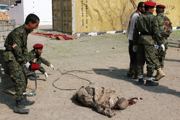 Soldiers are seen near to a dead body lies on the ground after a missile attack on a military parade during a graduation ceremony for newly recruited troopers in Aden