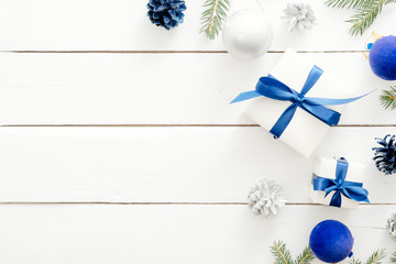 Modern Christmas flatlay composition. Gift box with blue ribbon bow, decorations, fir tree branch on white wooden background. lat lay, top view, copy space. New year, Christmas, winter concept.