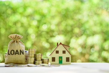 Mortgage-backed security MBS, financial concept : House model, stacks of rising coins, loan bags on a table over green background, depicts raising fund from a bank to buy home or properties or assets