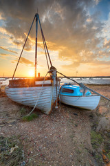 Wall Mural - Stunning sunset over old fishing boats on the shore at West Mersea,