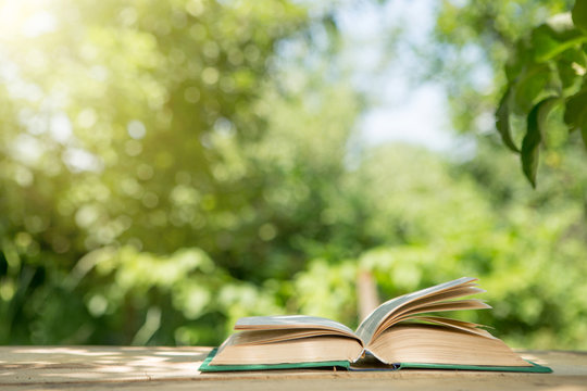 Studying in summer concept. Open book on a wooden table in a garden, sunny summer day