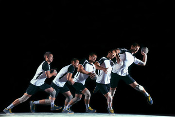 Caucasian young handball player in action and motion in mixed and strobe light on black studio background. Fit professional sportsman. Concept of sport, movement, energy, dynamic, healthy lifestyle. Wall mural